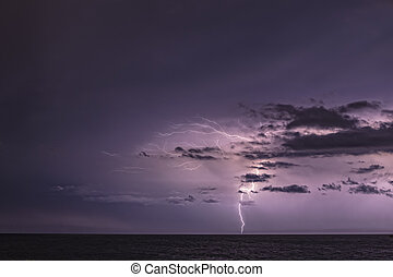Lightning and Clouds - Lightning bolt hits the horizon just...