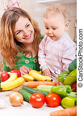 Happy mother with baby daughter preparing vegetables