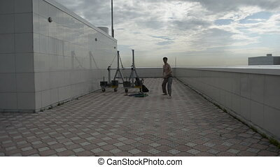 Man practices yoga on the roof. Complex military exercises...