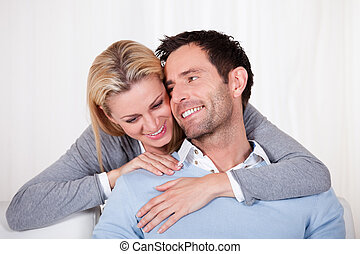 Affectionate couple relaxing on a sofa with the mans arm...