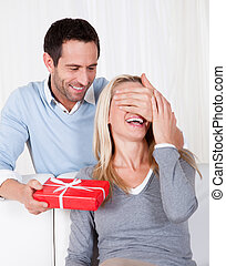 Man giving his wife a surprise gift at home