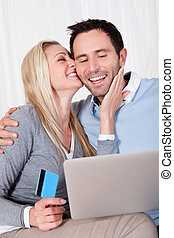 Couple having fun shopping online sitting laughing as they...