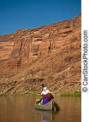 Man paddling canoe in desert canyon river