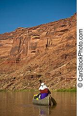Man paddling canoe in desert canyon river