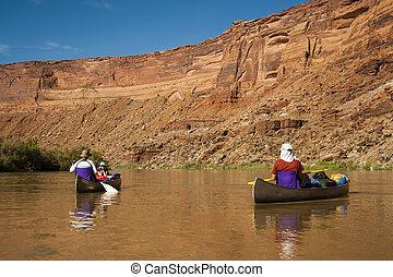Family in canoes on desert river