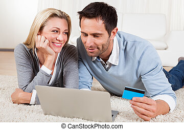 Young couple shopping online - Attractive young couple lying...