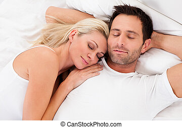 Couple in love - Beautiful young couple relaxing in bed at...