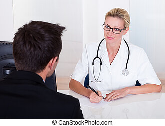 Female doctor consulting with a patient - Attractive female...