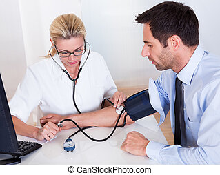 Doctor taking a patients blood pressure - Attractive young...