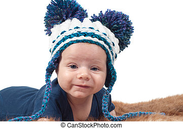 Cute baby in knitted hat with big pom-pons watching on you