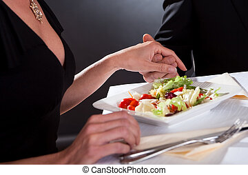 Man and woman holding hands over dinner - Cropped view image...