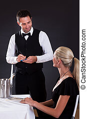 Waiter taking order from woman in restaurant