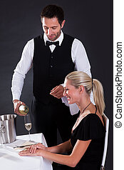 Waiter serving champagne to a beautiful blonde woman seated...