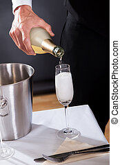 Waiter serving champagne to at the restaurant