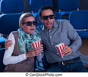 Couple reacting to a 3D movie - Couple sitting in seats at a...