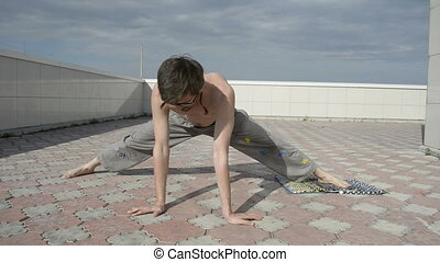 Man practices yoga on the roof. Do the splits, the emphasis...