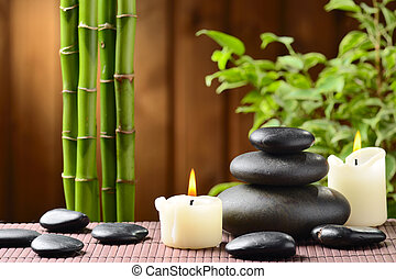 spa concept - zen basalt stones and bamboo on the wood
