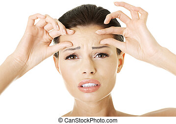 Woman checking her wrinkles on her forehead - isolated on...