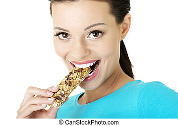 Young woman eating cereal candy bar - Young woman eating...