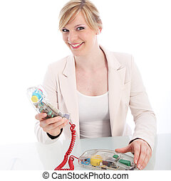 Smiling woman using a landline telephone with a bright red...