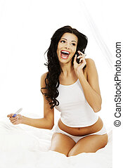 Happy beautiful woman on bed with pregnancy test in hand...