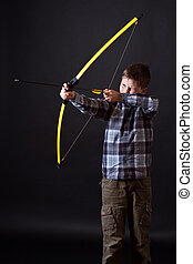boy shoots a bow on a black background