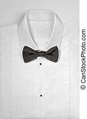 Luxury white tuxedo shirt and bowtie close up on white...