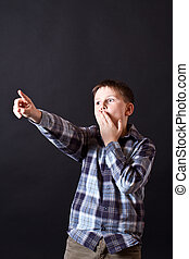 surprised boy - Surprised boy points his finger at a black...