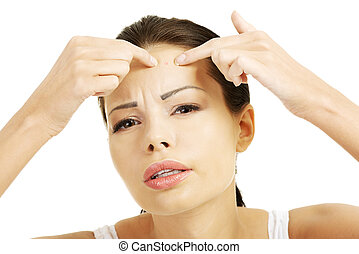 Young woman with pimple on her face Trying to squeeze it...