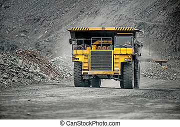 Yellow mining vehicle driving in the pit