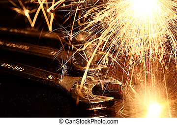 Closeup of iron spanners set and sparks light