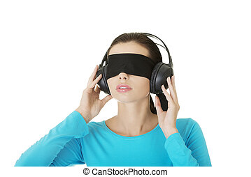 Blindfold attractive woman with headphones listening music