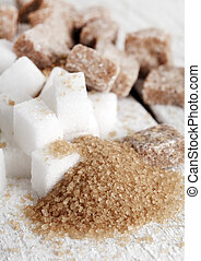Little heap of white and brown sugar cubes on a white wooden...