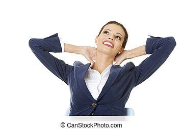 Female executive relaxing with hands behind head