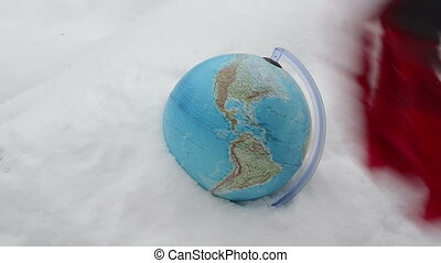 hand earth globe snow - Hand with leather gloves put red...
