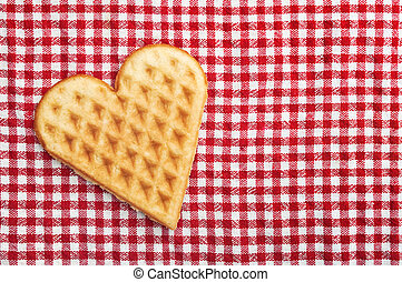 Heart shaped galette cookie on red and white checkered table...