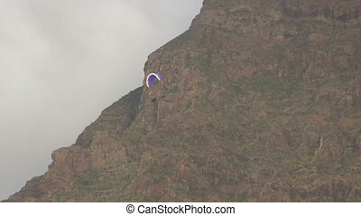 Hang Gliding near a cloudy mountain.