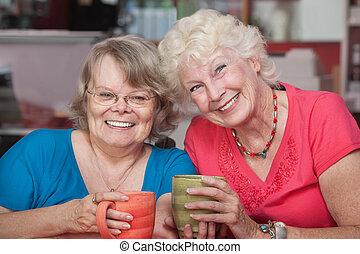 Pair of Smiling Friends - Two happy senior friends with mugs...