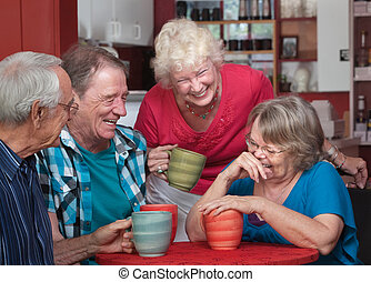 Laughing Friends in Coffeehouse - Group of laughing seniors...