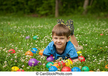 A five year old boy laies in the grass surrounded by...