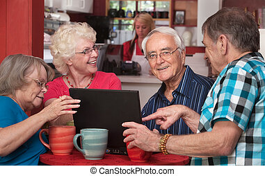 Seniors Having Fun with Computer in Cafe - Group of four...