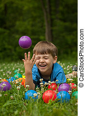 A five year old boy laies in the grass surrounded by colorful toy balls. The boy has expressions of fun and happiness.