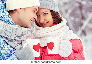 Winter romance - Portrait of happy young couple holding cups...