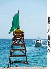 Lifeguard on a beach - Lifeguard sitting on beach watchtower