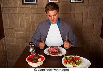 eat a beef steak - man holding a knife and a fork ready to...