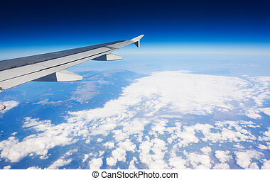airplane - Wing of airplane flying above the clouds in the...