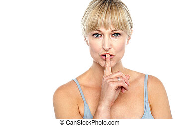 Attractive middle aged woman gesturing silence isolated...