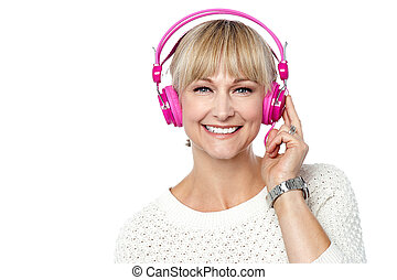 Portrait of a cheerful woman with headphones on, enjoying...