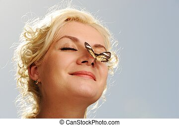 Beautiful butterfly sitting on a woman nose