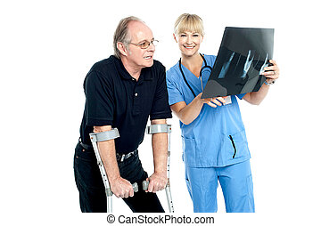 Surgeon showing x-ray sheet to her patient
